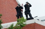 Armed police keep watch from the roof of