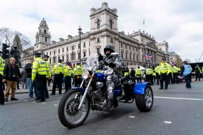 A motorcyclist rides past police officers in central London on April 12, 2019, during a protest against the Bloody Sunday prosecution of Soldier F and in support of all Veterans. - A former British soldier faces murder charges of two people after troops opened fire on civil rights demonstrators on Bloody Sunday in Londonderry in 1972. (Photo by Niklas HALLE'N / AFP)NIKLAS HALLE'N/AFP/Getty Images